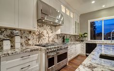 Alaska White Granite makes a stunning counter and backsplash to the Antique White cabinetry