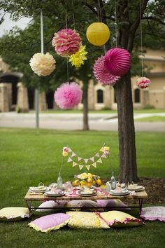pink and yellow sunshine and sweet lemonade theme birthday party outdoor setting for table with tissue poms rosettes and paper lanterns hanging from the tree