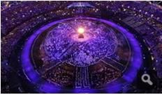 """117c: The photo was labeled under """"very nice images"""" of the Olympic stadium in London. It's an overhead view of the stadium all lit up at night, framed in a very grand and bright way. It shows the importance of the entire Olympic process to the world because of its massive scale."""