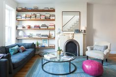 Innovative Floating Bookshelves method New York Transitional Living Room Inspiration with blue area rug blue sofa framed mirror mirror above fireplace pink pouf reclaimed wood