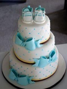 pastel con moños color azul y unos zapatos de color azul y blanco en la parte superior