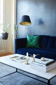 Elegant living room with a gray wall, a blue velvet sofa, and a marble table