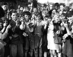 Children from east London hold up pieces of anti-aircraft shell fragments they have collected as scrap for the war salvage effort, 1940s