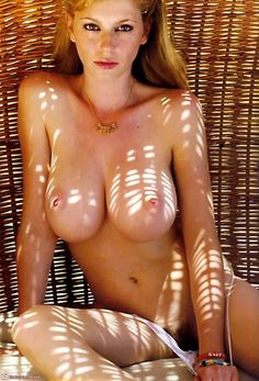 Stunning redhead sitting in a wicker chair covered in freckles, with big beautiful pale boobs and pink nipples