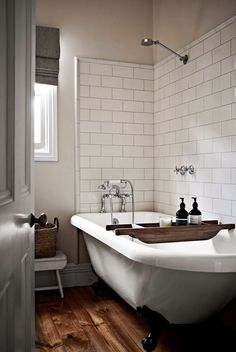 A wall of shower tile surrounding a claw-foot tub helps minimize splashing