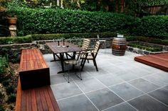 love this! linear, cold gray tiled patio w/ warm wood benches and deck surrounding