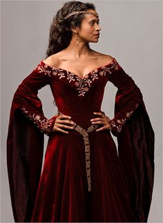 BBC Merlin Series 5. Angel Coulby as Queen Guinevere in red velvet gown with gold embroidery.