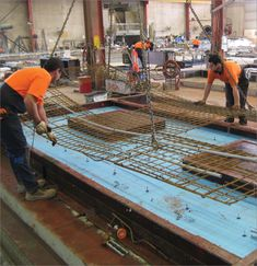 Photo of the construction of a precast concrete panel in the factory. The panels have the steel reinforcement frame, and cut-outs for windows and services. The panels are ready to be poured.