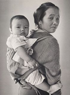 May Yang of Sheboygan, Wisconsin  with her son John Lee who is carried in a traditional Hmong baby carrier, 1981  John Michael Kohler Arts Center, Permanent Collection