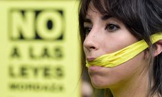 En Espagne, 800 € d'amende pour la photo de policiers garés sur une place handicapée [Une manifestante espagnole proteste contre la loi de sécurité espagnole, le 30 juin à Madrid].