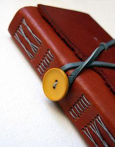 Costurar por cima do couro, capa. Fechar com botão na lateral do caderno e não na capa.