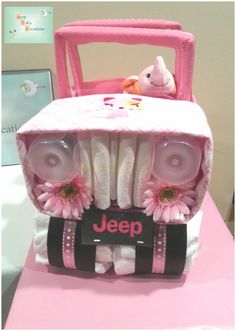 The jeep diaper cake is New Baby Creations' latest design featuring two receiving blankets, two baby bottles, two baby washcloths and approximately 40 diapers.  Floral headlights and decorative ribbon complete this awesome diaper cake!