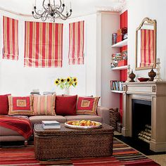 .Love this red and white family room. Love the simple red stripe shades. the patterns on the pillow and the red paint behind the bookcase. The neutral walls, wall to wall carpet, modern sofa and basket coffee table and fire place calm the red. I would prefer art to the mirror over the fireplace, but I could live happily in this room