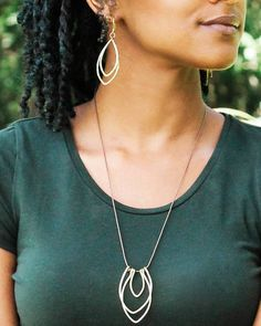 """Trades+of+Hope+-+++Product+Details:+++++ This+trio+of+metal+hangs+on+a+waxed+cotton+adjustable+cord. ++ Approx.+Measurements:+27""""+long,+2.5""""+trio+of+metal++ Material:++Brass+wire+and+waxed+brown+cotton+cord++ Color:+Gold+&+Brown+++  ++Artisan+Information…"""