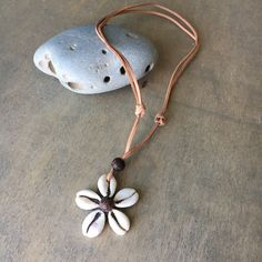 "A Flower from the Garden in the Sea, This Flower is made from Cowrie Shells and Brown Wood Beads on an imitation leather cord. Description: Bead Necklace: Adjustable Slip knot from 16""-24"" Long Pendan"