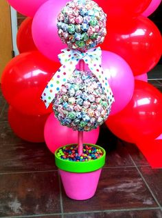 Decoration for Candyland Prom 2012  (dum dum topiary)  Use a foam topiary and just push the dumdums through foam. I had to cut the dum dum sticks for the top ball.  The bottom is skittles, but any candy would work. (Topiary, flower pot, and ribbon came from Hobby Lobby)