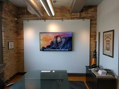 """65"""" Panasonic Display connected to a MAC Mini with wireless mouse and keyboard. Commercial real estate office downtown."""