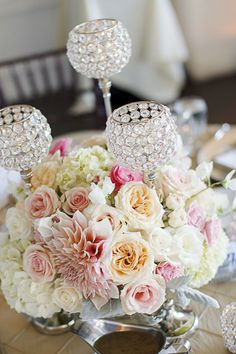 The table centerpieces featured crystal candleholders and dahlia and garden rose floral arrangements.