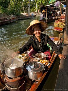 Thailand, Bangkok, Woman selling food at Damnoen Saduak Floating Market.