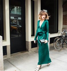Carmen Hamilton wears an emerald green silk dress with strappy heels