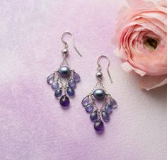 The dreamy blues of evening and the drama of midnight are captured in these freshwater pearl iolite and amethyst chandelier earrings, made by Thoi Vo .
