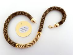 A perfect gift: a beaded rope jewel, a Statement necklace made of beautiful frosted bronze and golden beads. A gorgeous jewel for all the lovers of warm colors. I created this beaded necklace crocheting a chain of 7 Japanese Toho beads, size 8/0, with brown lisle according to the tubular technique. Golden cap ends. Hypoallergenic metal clasp. I used frosted bronze beads for the background; then I created one band, made of galvanized golden beads with a beautiful metallic effect, placed ...