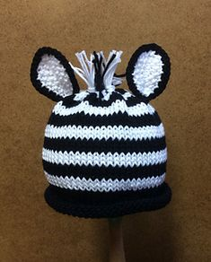 This easy, striped baby-topper is knit in-the-round. The ears are knit separately and sewn-on. The zebra's fringe-mane is made using the same yarn as the hat. A crochet hook (size H) was used only to pull the fringe through the hat to make the mane.