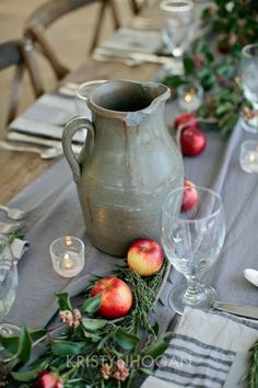 Rustic pottery jugs combined with linen, fruit, and herbs