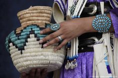 Close-up of woman wearing Native American jewelry holding basket, Gallup, New Mexico, USA.