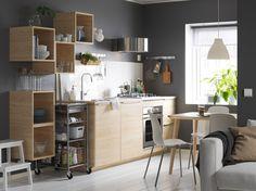 Серо-белая кухня со шкафами и стеллажами из светлого дерева.