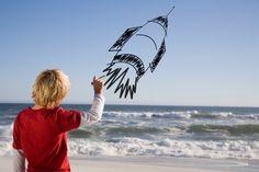 Stock-Foto : Boy drawing digital image or rocket on sky at beach