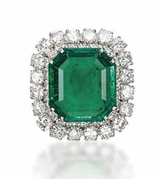 AN EMERALD AND DIAMOND RING, BY BULGARI   Centering upon a rectangular-cut emerald, weighing approximately 6.92 carats, in a double row of brilliant-cut diamonds, mounted in platinum, ring size 7 with ring sizer, in green leather Bulgari case  Signed Bulgari