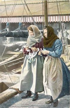 Postcard showing 'Herring Lasses off Duty' - two typical 'Scotch' Girls (as they were known) off duty, knitting needles in hands.  This was a regular sight in town, seeing them walking around town, knitting and chatting as they went. Every spare moment was taken up with knitting when they weren't packing the fish barrels. Knitters created their own stitch patterns often taking ideas from the Scottish herring girls' work.  Norfolk England, Sheringham Museum