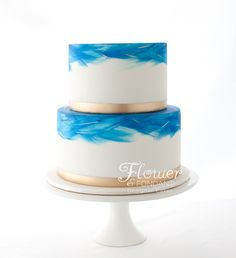 A simple blue watercolour & gold wedding cake which was finished with flowers provided by the brides sister.