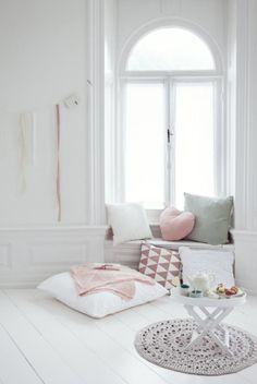 Wielkie poduchy i szydełkowany dywanik tworzą romantyczną atmosferę.