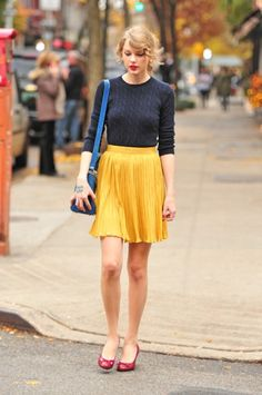 Marigold skirt paired with a navy cable sweater and burgundy shoes