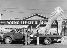 Silver Slipper electric sign in front of the Young Electric Sign Company (Las Vegas), University of Nevada Las Vegas Libraries. Electric Signs, Sign Installation, Silver Slippers, Neon Museum, Ghost In The Machine, Vintage Neon Signs, Las Vegas Blvd, Sign Company, Old Signs