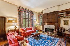 Living room with wood paneling, fireplace, red couches, patterned rug, framed artwork.