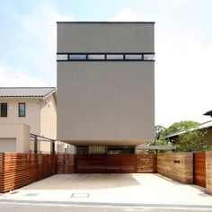 The cantilevered upper storeys of this house in Osaka by Japanese architect Shogo Iwata hover above a driveway.