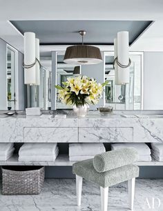 Hervé Van der Straeten sconces overlook the room's marble vanity; the stool is clad in a Perennials terry cloth.
