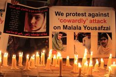 Pakistani people light candles in front of a portrait of Malala Yousafzai as they praying for her well-being in Lahore