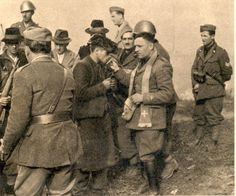 Last confession. A Yugoslavian partisan going to be executed as saboteur, kisses the Cross after the last confession to the Black Shirts chaplain.
