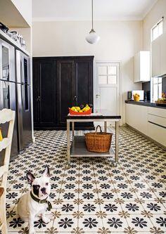 Cocina antigua reciclada con pisos calcáreos, equipamiento de acero inoxidable y detalles vintage en tonos crema y marrón. Mesada de granito negro Brasil. Un bulldog francés mira a la cámara atento :)