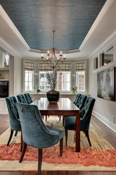 A paneled off section of the ceiling wallpapered to center the room on the dining table