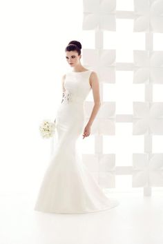 Mikaella Bridal Gowns available at The Bridal Gown IN Otley, Leeds. Heavy mat  satin #wedding gown high necked  with deep scoop back. #Fishtail shape with feather and flower detail at waist.  Very Audry Hepburn. for the confident bride who wants to wear the dress not let the dress wear her.