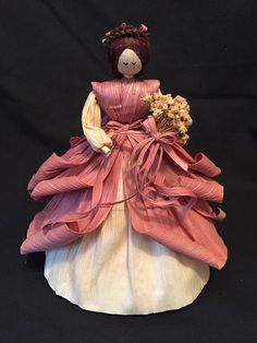 Cornhusk doll with mauve skirt, bodice and bows. Skirt has extra layers so more curls. Underskirt is natural color. Hair is corn silk done in curls. Holding flowers but I could change it to holding something else if requested. Stand 9 approximately.