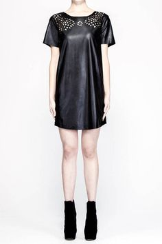 Short sleeve t-shirt style relaxed fit dress in black. Pu leather look dress with laser cut out at front. Back overlapping pu panels. Jersey in black at back. Crewneck round collar. 50% pu 50% polyester. Cold hand wash only.  Style it: A perfect day dress to be styled with a perforated clutch and silver accessories.
