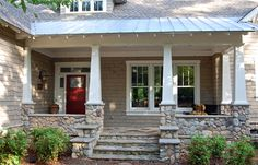 Great farmhouse craftsman style porch with the metal roof, craftsman columns, and beautiful rock support posts and steps