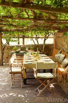 Situated directly under a manicured pergola, a rustic dining table provides the owners of this Tuscan farmhouse with the perfect place to enjoy an outdoor meal. Tour the rest of the home.