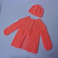 Cute handmade set for 7 years old girls made of pink yarn. It is consisted of a sweater and a lovely hat. The sweater has five white buttons on the middle, and three knitted flowers on the top of the left side.